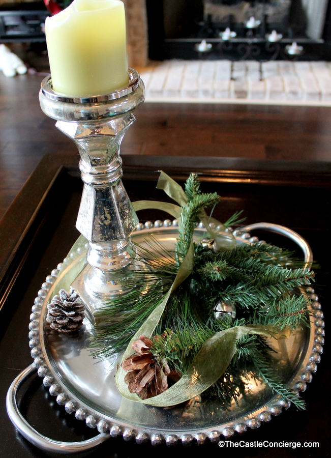 A silver platter and candlestick add a touch of elegance to the coffee table