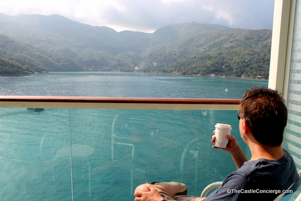 Passenger on Royal Caribbean enjoys coffee on outdoor balcony while heading into a new port.