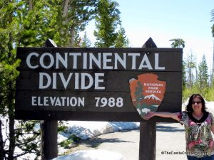 Take a picture at the Continental Divide sign near Riddle Lake, Wyoming close to the South Entrance to Yellowstone.