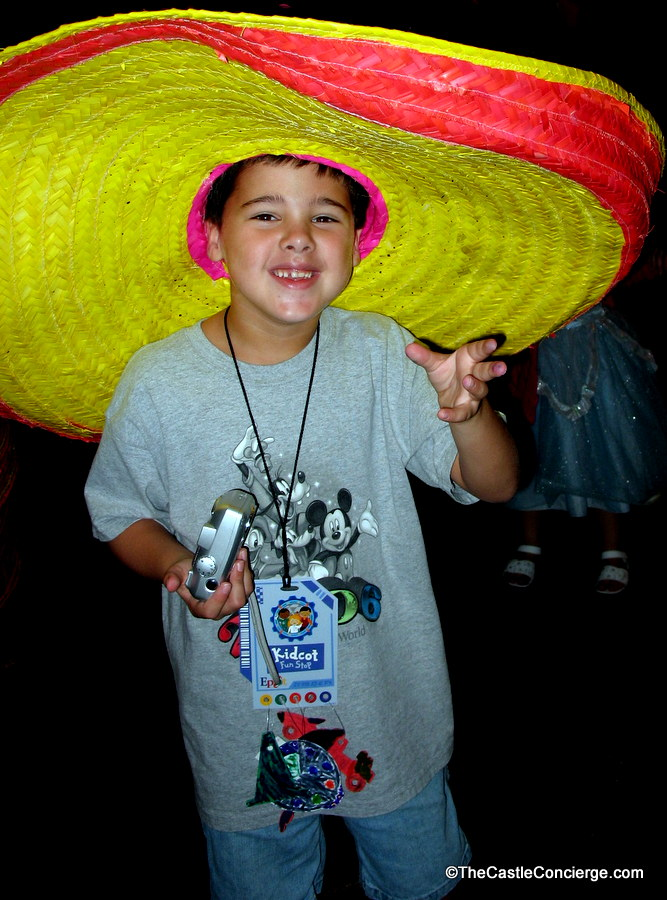 Child posing with sombrero inside Epcot's Mexico