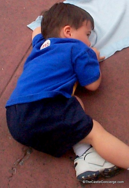 Our exhaused child decides to take a nap on the sidewalk inside the Magic Kingdom at Walt Disney World.
